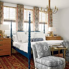 A hand-carved four-poster bed in deep navy stands out against walls painted a soft neutral by Benjamin Moore. Natural wood and copper hues add richness and warmth. | Coastalliving.com