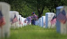 Tiger Scout Christian Pavlock, 7, carries American flags in honor of the Memorial Day holiday at Long Island National Cemetery in Farmingdale, New York on Saturday, May 23, 2009. (AP Photo/David Goldman)