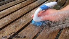 Use a scrub brush and clean water to rinse the cleaner from a fine teak table. Photo Credit: Tim Carter