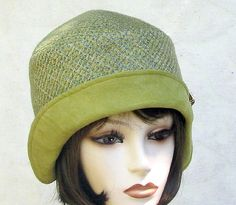 Roaring 1920s flapper vintage reproduction cloche hat made in nubby chenille heavy fabric. A gorgeous color combination in a apple green suede cloth brim with the crown in an array of multiple shades of complementary olive greens with diagonal threads in contrasting peacock and teal blues. I have detailed this hat with an elegant vintage pin in a cluster of lemon yellow flowers with pale green rhinestone centers. The hat is lined in a complementary green satin. My hats are 100% handcrafted…