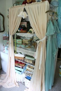 Target garage-y shelving unit covered by silk curtains. So pretty !