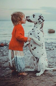Little girl kissing dog at the beach...this dog knows little one is cool.  Subject...DHM