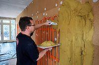 Het aanbrengen van de leemstucwand met lage temperatuurs verwarming voor de stralingswarmte op de zitplaatsen in de woonkamer