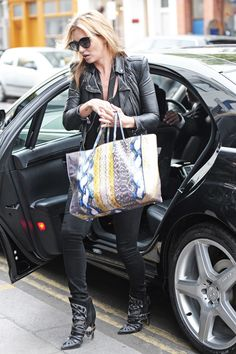 Kate Moss wears all black head to toe and carries a snake printed tote