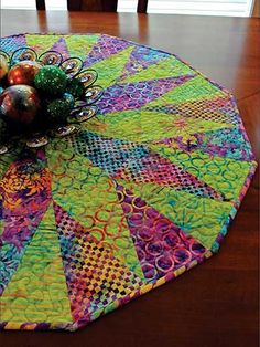 "Truly versatile table topper or tree skirt! This delightful topper can be made in holiday colors or colors that coordinate with your kitchen for year-round use. The pattern includes 3 different sizes -- 24"", 36"" or 48"" diameter -- so you can make a topper for your table, a skirt for your tree or both! Use the Creative Grids 30° Triangle Ruler so cutting is a breeze."