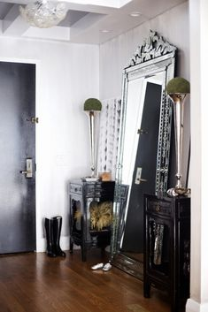 Glamorous entryway with leaning Venetian mirror and black door.