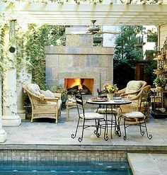 Two thumbs up to this outdoor living space right next to a pool! Would change the furniture but like the fireplace and trellis.