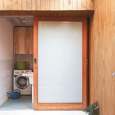 Aqui, fcam a lavanderia e o lavabo, ocultos pelas portas de vidro leitoso (Decorpisos). Elas correm de um lado para o outro na hora de dar acesso aos espaços. Esquadrias de garapeira da Mercosul.