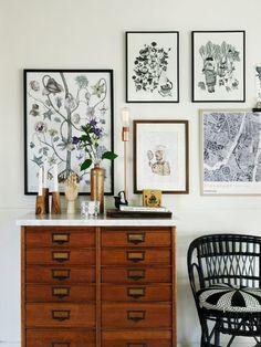 Mix de quadros, poltrona preta e cômoda na sala