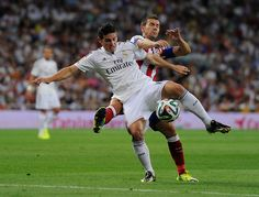 """James Rodriguez is tackled by Gabriel Fernandez alias """"Gabi"""" during the Supercopa first leg match between Real Madrid and Club Atletico de Madrid at Estadio Santiago Bernabeu on August 19, 2014 in Madrid, Spain."""