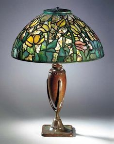 A 'TULIP' LEADED GLASS AND BRONZE TABLE LAMP Tiffany Studios, circa 1910 21¼in. (54cm.) high, 157/8in. (40.3cm.) diameter of the shade, with finial the shade tag stamped TIFFANY STUDIOS NEW YORK, the 'crutch' base stamped TIFFANY STUDIOS NEW YORK 444 with curvilinear Tiffany Studios monogram