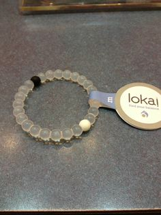 Lokai - black bead has sand from Dead Sea (lowest point).  White beach has water from Mt. Everest (highest point).  Life in balance.