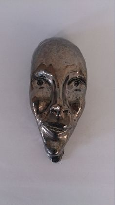 Wall hanging ceramic mask in metallic glaze by PArmstrongCeramics