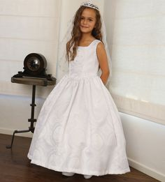 An awesome fashion creation, a great Communion dress from Angels Gaarment for your girl. Gorgeous cross motif embossed satin dress. Rhinestone accented cross on the front of the bodice. It has adjustable lace up corset back. Organza bolero is included. Fu