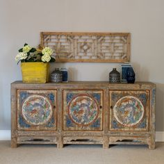 A unique and pretty Chinese pine Sideboard with colourful hand paintings, which originated in the Beijing province c.1900    This long sideboard has three single cupboards, each housing a removable shelf. The cabinet is natural wood with traces of blue lacquer, but the doors feature colourful circular hand-pantings featuring goldfish, which are a popular Chinese symbol said to bring abundance in to your life.#sideboard #storage #blue #rustic #distressed #oriental #chinese