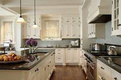 Dark countertop, dark flooring, white cabinets