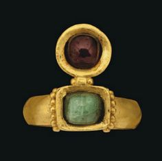 A ROMAN GOLD, EMERALD AND GARNET RING   CIRCA 4TH CENTURY A.D.   With solid gold plain hoop, slightly raised rectangular box-set bezel with row of granulation either side, set with a cabochon emerald, the circular box-set bezel projection set with garnet bead  Bezel ¾ in. (2 cm.) wide