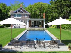 This Cape Cod home has an inviting backyard space with a traditional pool and seating area. The outdoor space is great for relaxing and enjoying the summer weather.