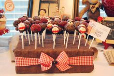 DIY pop stand: The cake pop stand was made by stacking 3 styrofoam rectangles together and covering them in brown burlap, then adding some red and white gingham ribbon and a brown button.