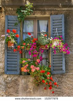 Vintage window with open wooden shutters and fresh flowers - stock photo