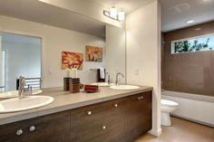 meuble salle de bains en bois à poignées rondes et carrelage beige