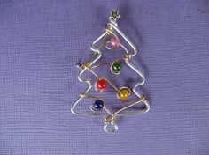 This design was created by drawing it first and then, with a lot of practicing, make it with the wire. It is made of a wire that won't tarnish and doesn't need to be cleaned. The tree has little colored beads for ornaments and a little star bead on top. Check the coin photo for the approx. size! (approx. 2 inches high). Perfect for the holidays and stocking! Makes a very original gift also!!! *