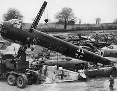 The wrecks of Luftwaffe aircraft in a British scrapyard, 24 February 1942. The fuselage of a Junkers Ju 88 is being lifted by a crane.