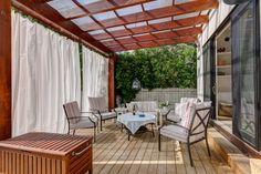 Holzpergola mit Sonnenschutz-Gardinen aus lichtundurchlässigem Stoff