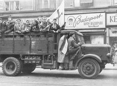 truck with Hungarian youths, holding white flag with Red Cross marked in by blood speeding through revolution torn Budapest, Oct. 29, 1956.