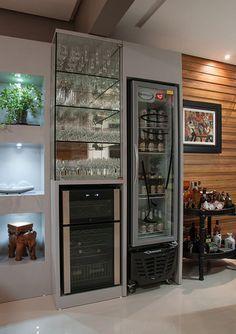 O cliente desejou a criação de um espaço entre a churrasqueira e as salas de jantar e estar que pudesse acomodar uma área de bar – com adega, cervejeira e cristaleira.