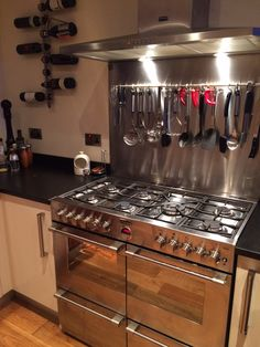 Sarah's gorgeous Stoves Sterling range cooker, hood and splashback in stainless steel, proudly made in Britain. Complemented by a handy utensil rail (and wine rack!), this range features enough room for all the family's kitchen needs.