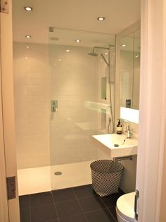 Photo Gallery For Website Clean modern small bathroom with seamless glass shower divider and dark floor tiles
