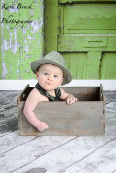 6 month baby boy photo shoot session idea. Baby sitting in a crate with a hat on and his dad tie. Six month old pictures for fun photography ideas.