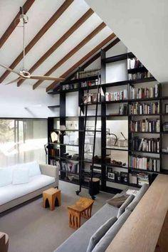 une grande bibliothèque murale et noire dans le salon spacieux