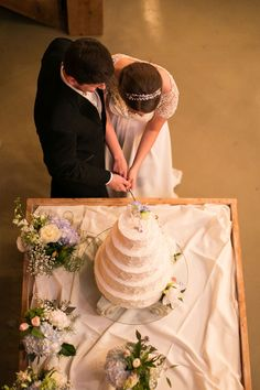 The groom and bride cut into a buttercream wedding cake at their rustic wedding reception.