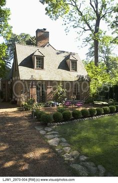EXTERIORS: part of gravel driveway with stone edging  front patio of French country style home boxwood hedge