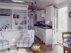 Soft blues and whites create a wonderful beach and nautical themed look for this cozy cottage. Note the ship painting, starfish and seahorse pillow, and the big starfish decorating the kitchen walls.
