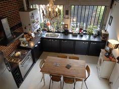Zoevox Design Kitchen -  Le style industriel y est affirmé avec des meubles de rangements en métal sur-mesure dotés de  poignées «métro», un mur en brique rouge et des pièces d'électroménager en inox (www.smeg.fr)... . Inattendus, un lustre à pampilles et une lampe à poser, emblématiques des codes bourgeois du 18 siècle, viennent bousculer l'ensemble et donnent un cachet fou à la pièce.
