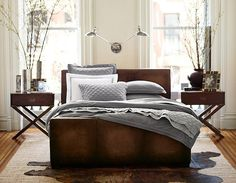 Layered tones of gray; textured bedding.  Pottery Barn rustic luxe line