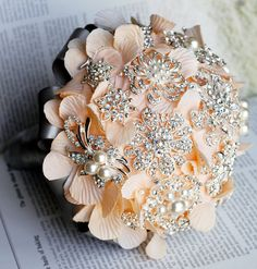 This is a deposit of $70 on a stunning rhinestone pearl posy. The total price for the bouquet is $300 and the remaining balance of $230 is due upon completion of the bouquet.         This vintage style bouquet features silver, peach pink, grey and rhinestone/pearl brooches, with double-row rhinestone and pearl chain on the handle.    Size: 7 inches in diameter (looking straight down)
