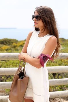 Jessie Chanes is wearing a sheer trim white dress from 6KS, bag from Alexander Wang and sunglasses from Dolce & Gabbana