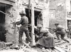 Troops clear out a German sniper nest, Caen, July 1944. KEN BELL, LIBRARY AND ARCHIVES CANADA—PA132727