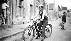 Une mécanicienne de fantaisie sur une Terrot 100 cm3 Type VM à cadre ouvert. Lancée en 1932, cette machine obéissait à la réglementation des B.M.A. (Bicyclette à Moteur Auxiliaire) datant de 1926. Limitées à 100 cm3, elle devaient avoir des pédales de mise en route, une vitesse maximum 30 km/h, un poids maximum de 30 kg.