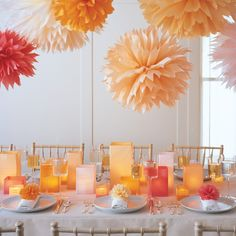 Dahlia-like pom-poms appear to float in the air, imparting a cheerful radiance to a rehearsal dinner, bridal shower, or casual reception. Echoing the vibrant hanging puffs, pom-pom napkin rings in citrus shades adorn each place setting. Square glass vessels covered in sunset-hued tissue cast a soft glow.