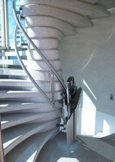 Montascale per scala a chiocciola all'interno di una vetrata. Il servoscala installato presenta colori moderni che si abbinano all'estetica del contesto.