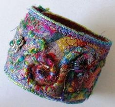 multicolored felted textile cuff. thick and thin textures give the piece a tactile look and feel. thick yarn is couched on. the edge is neatly finished by zigzagging over a piece of cording.