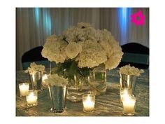 Para una boda de noche, pueden optar por un centro de mesa para boda con base de cristal cuadrada, alta y con velas. Las velas harán que el agua y el cristal brillen, dándole a la decoración de la boda un look muy elegante.