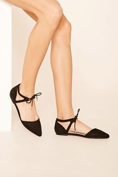 A pair of faux suede D'orsay flats featuring a lace-up ankle strap and a pointed closed toe.
