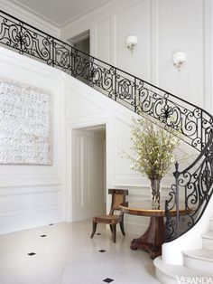 A curving iron staircase makes a striking impression in the entrance. Sconces, Marvin Alexander, Inc.; table, Rossi Antiques; walls in White Dove, Benjamin Moore; art, C. Gregory Gummersall.