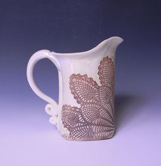The perfect iced tea pitcher or just water on the table, this pitcher is textured with a traditional pineapple lace impression which brings beauty to the table setting. When not being used for drinks it makes a graceful flower vase.  I make these pitchers by first rolling out a large slab of clay, cutting the pitcher template, rolling a lace doily into the cut slab of clay and then folding and smoothing into the unique and sturdy shape seen above. The glaze surrounds the lace impressed…
